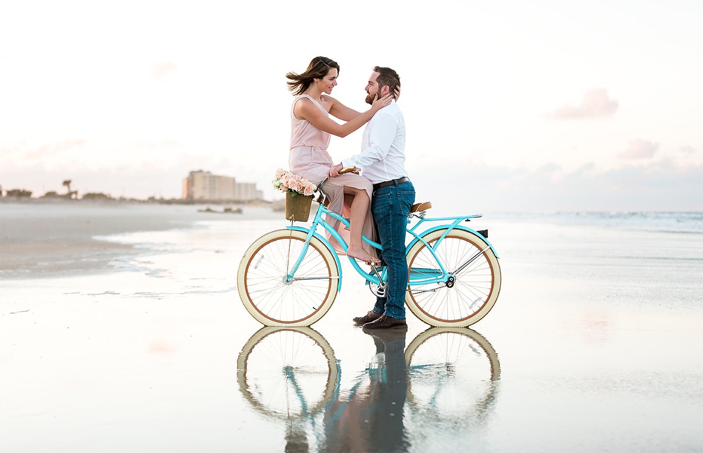 engagement pictures at the beach with a bike at sunset and basket filled with roses