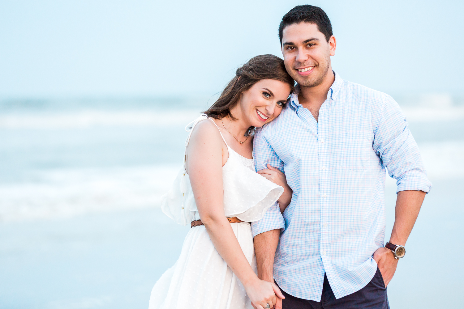 couple hugging during their engagement photoshoot at the beach