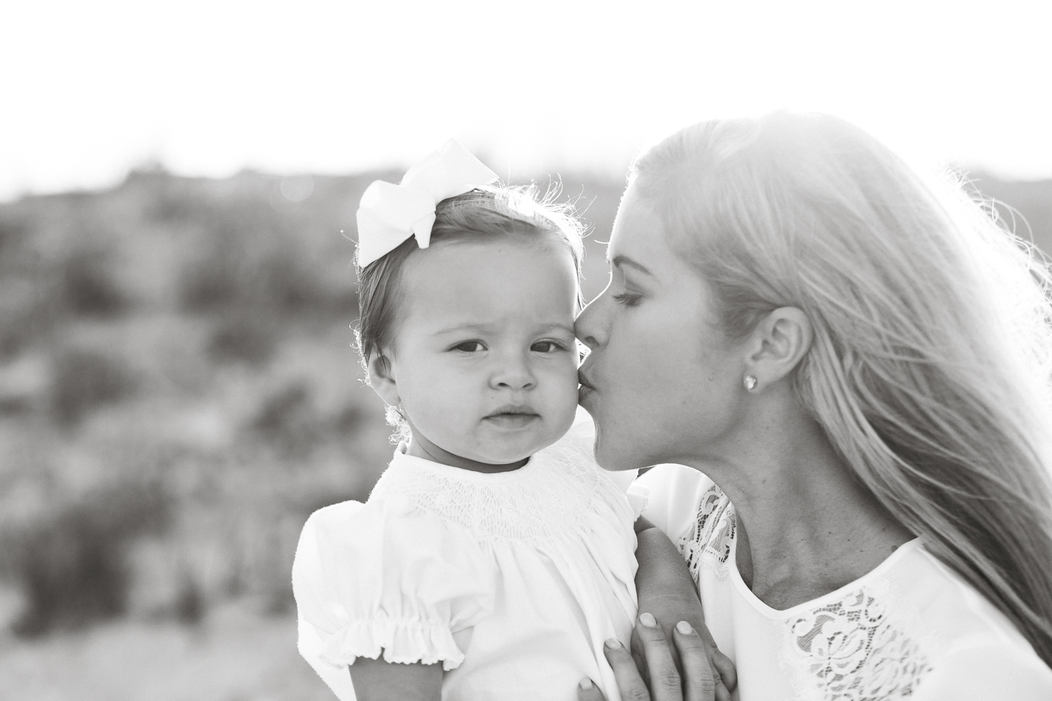mommy kissing her baby girl during family session