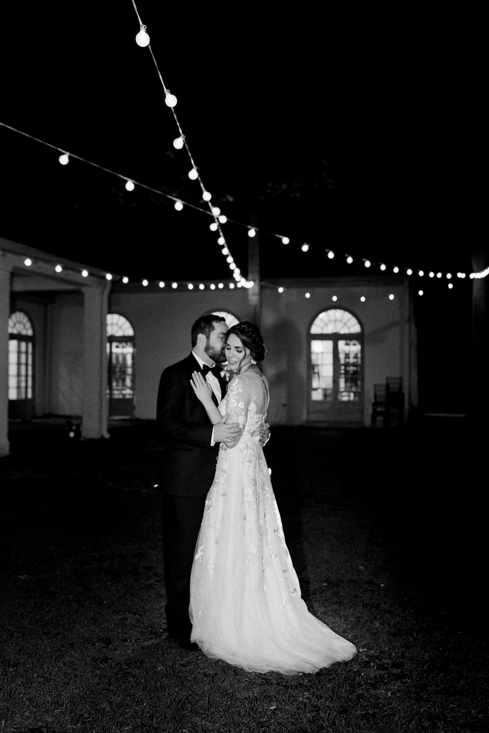 bride and groom pictures under the lights in the ribault club