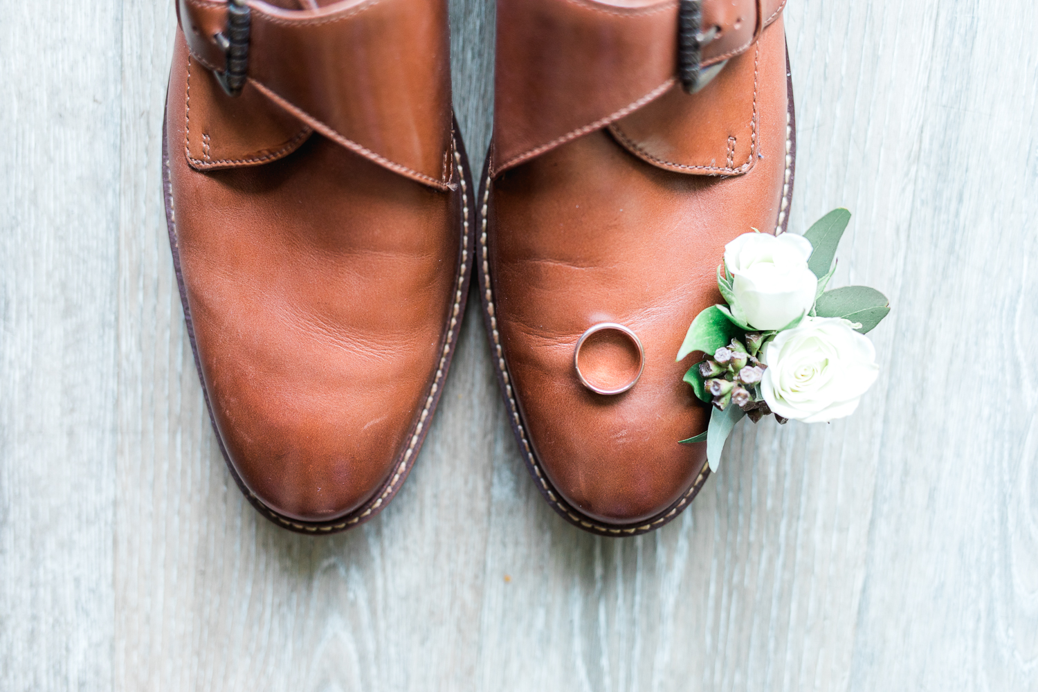 Detail shot of groom's shoes, boutonniere and ring