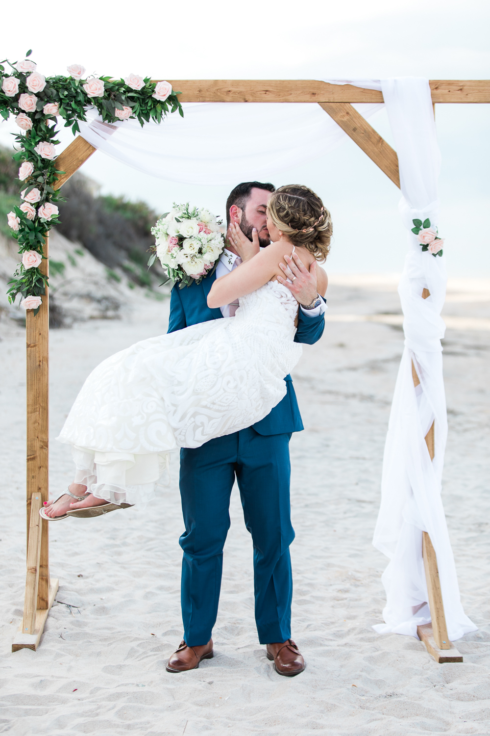 First kiss under the arch at the beach in Serenata Beach Club