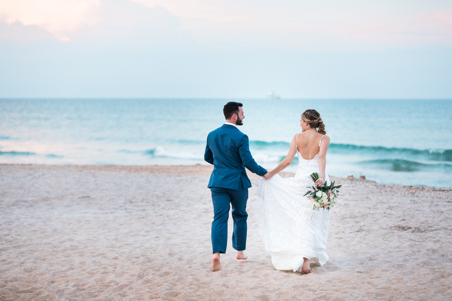 Bride and groom running at the beach during sunset