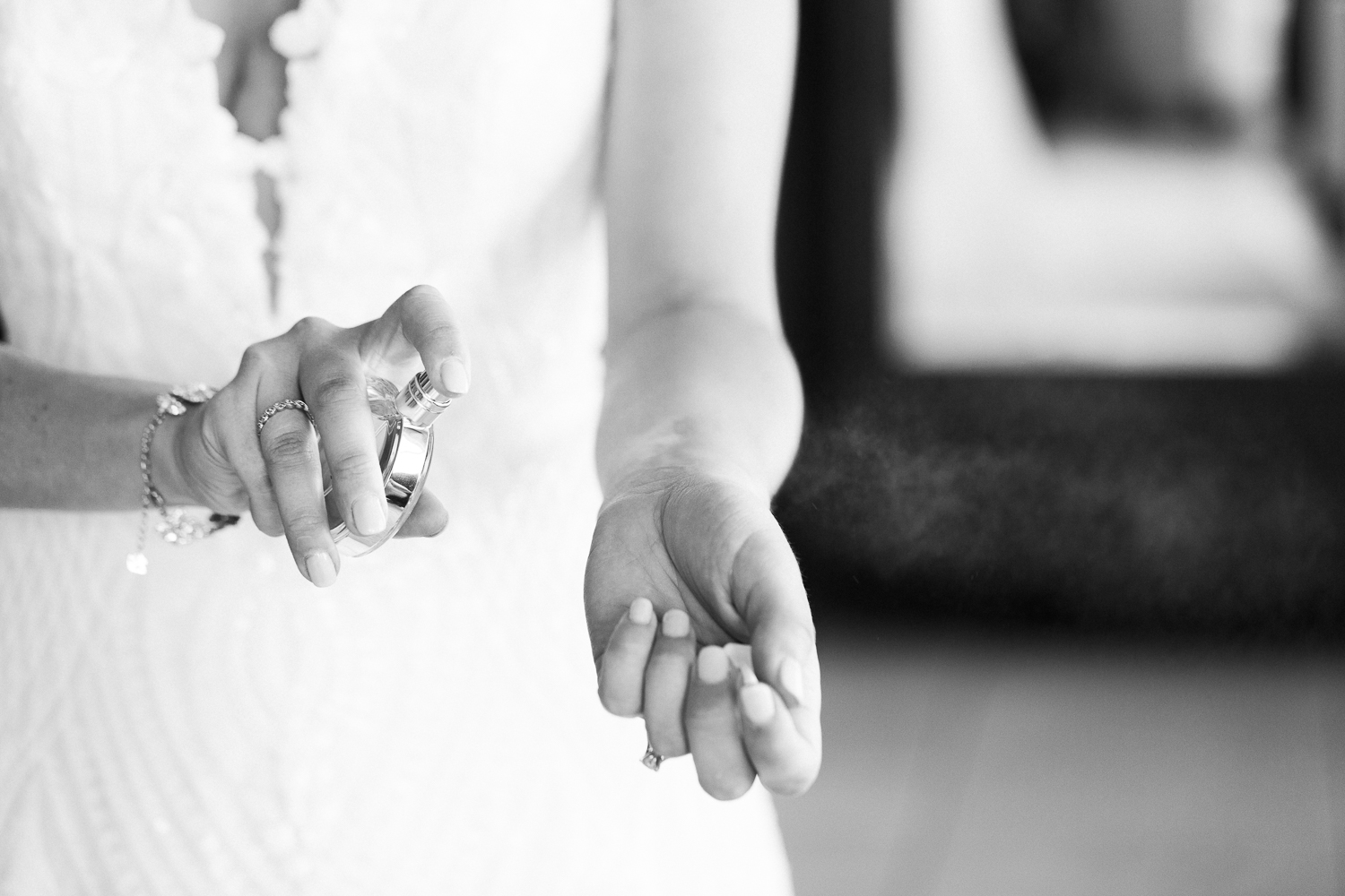 B&W image of bride spraying her perfume