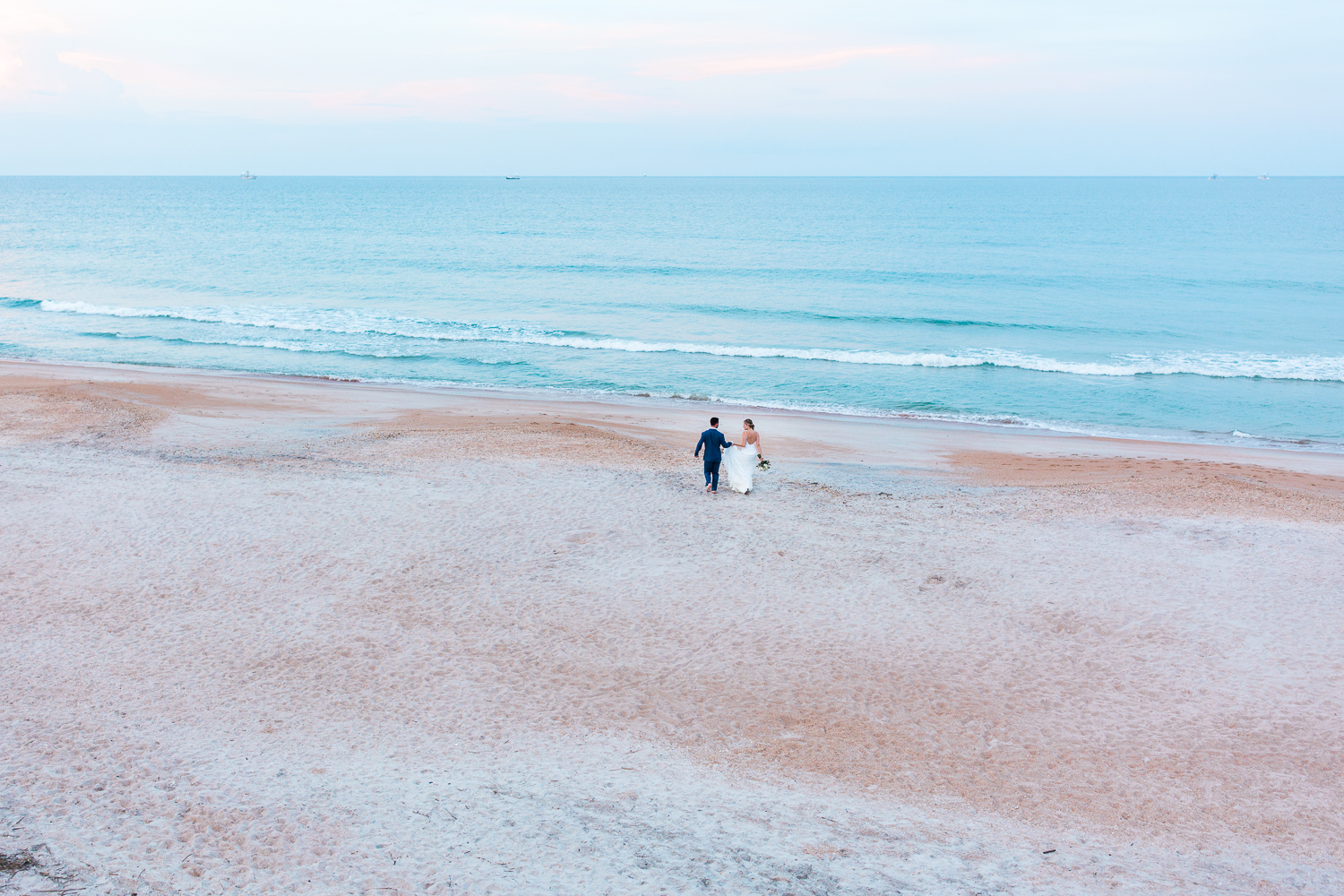 Stunning sunset picture of bride and groom running to the beach in Serenata Beach Club wedding