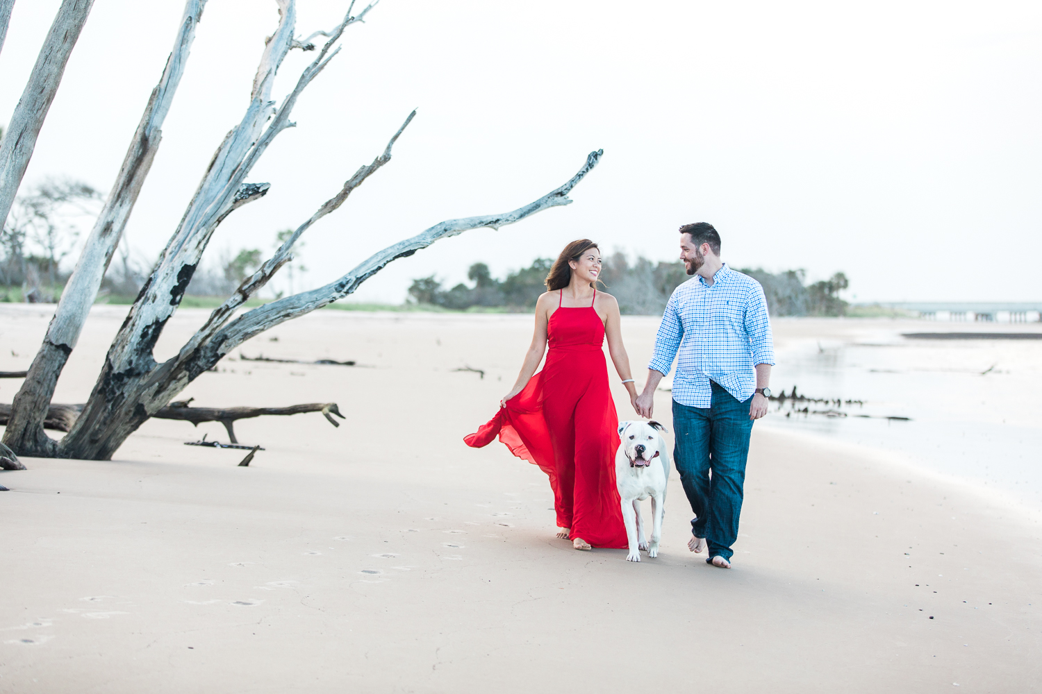 Walking at the beach with a dog during engagement session