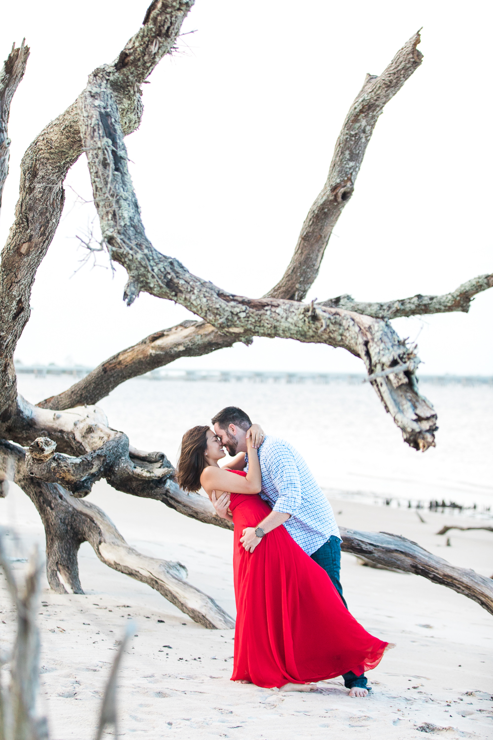 Engagement session posing ideas in driftwood beach near Amelia Island