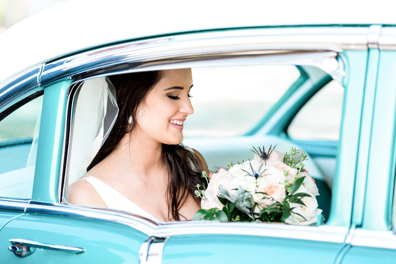 bride in a vintage car during her wedding in nocatee crosswater hall in ponte vedra, fl