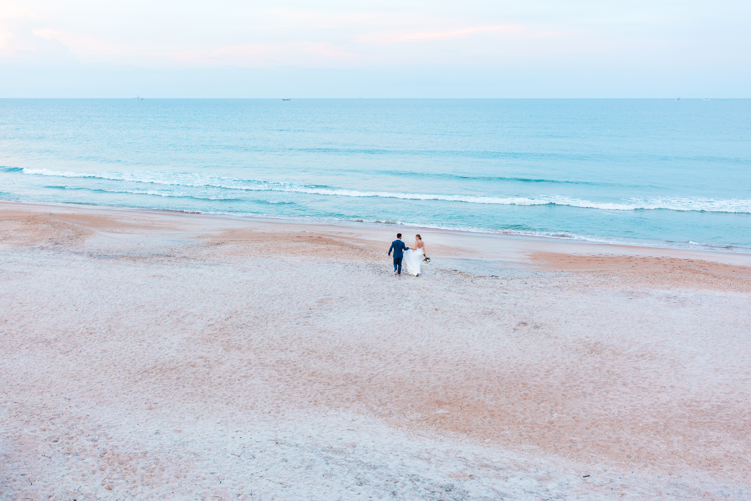 serenata beach club wedding picture ideas in st.augustine fl- bride and groom running to the beach during sunset