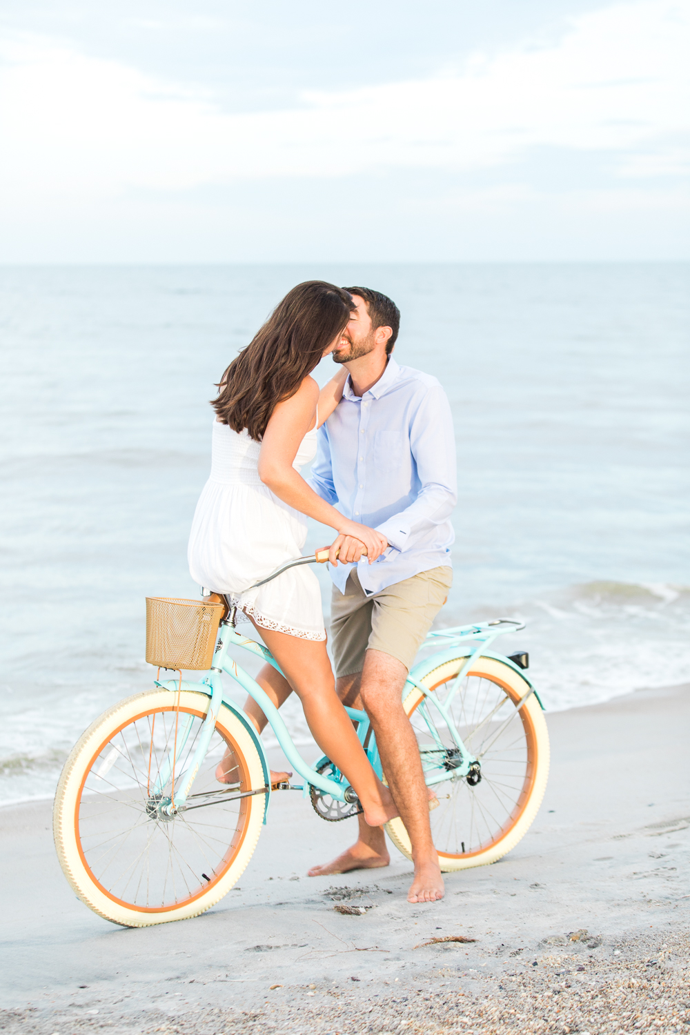engaged couple kissing on a beach cruiser bike at the beach during sunset