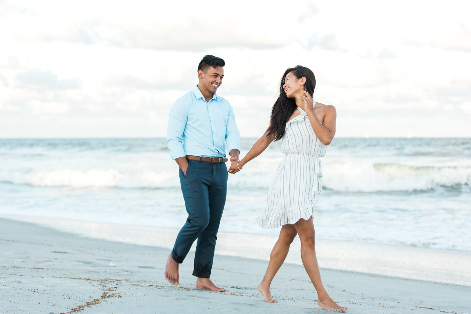 Engaged couple walking at thea beach during sunset in Jacksonville FL