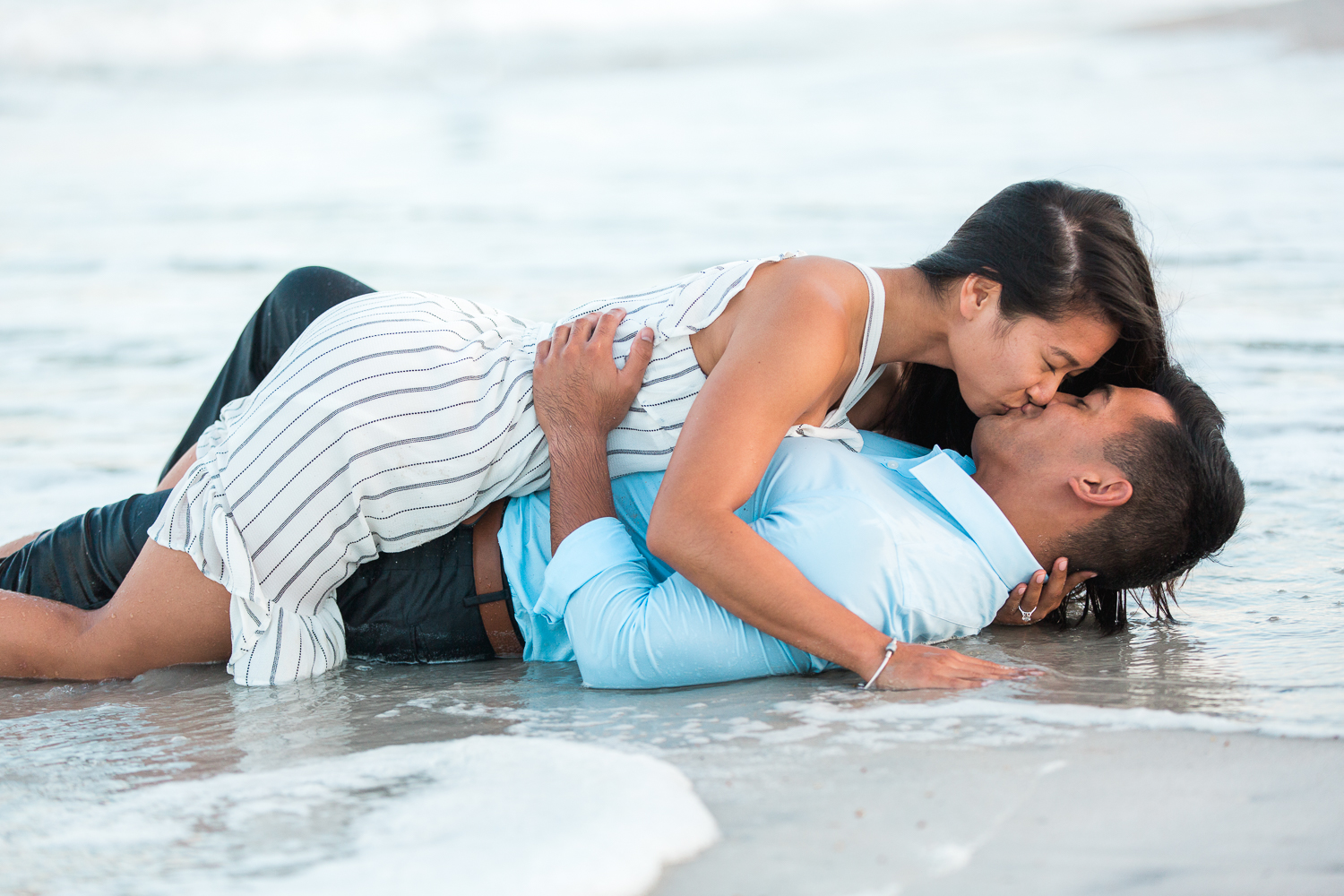 Engaged couple kissing in the ocean during their beach engagement session
