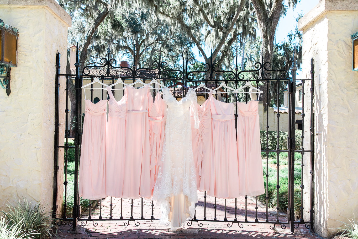 bride and bridesmaids dresses hanging on the gate at Epping Forest Yacht Club