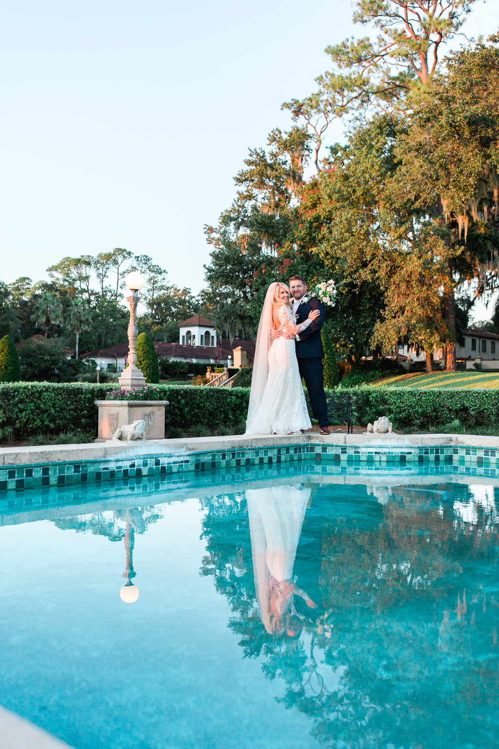 Bride and groom posing ideas - pool reflecting the newlyweds