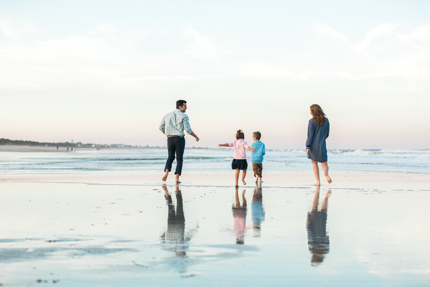 family running in the occean for a fall photoshoot