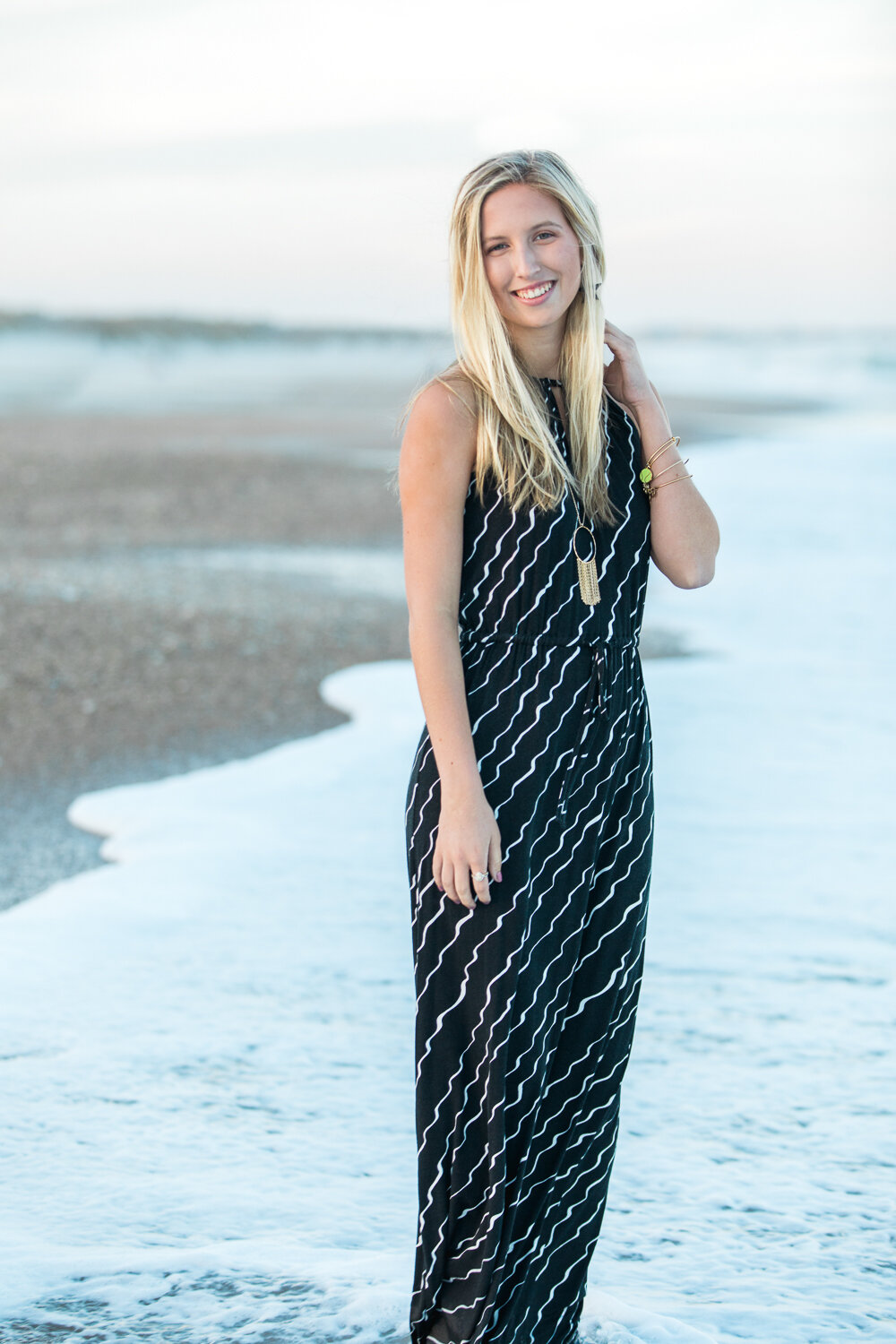 High school senior walking in the water during a photsohoot in jacksonville beach
