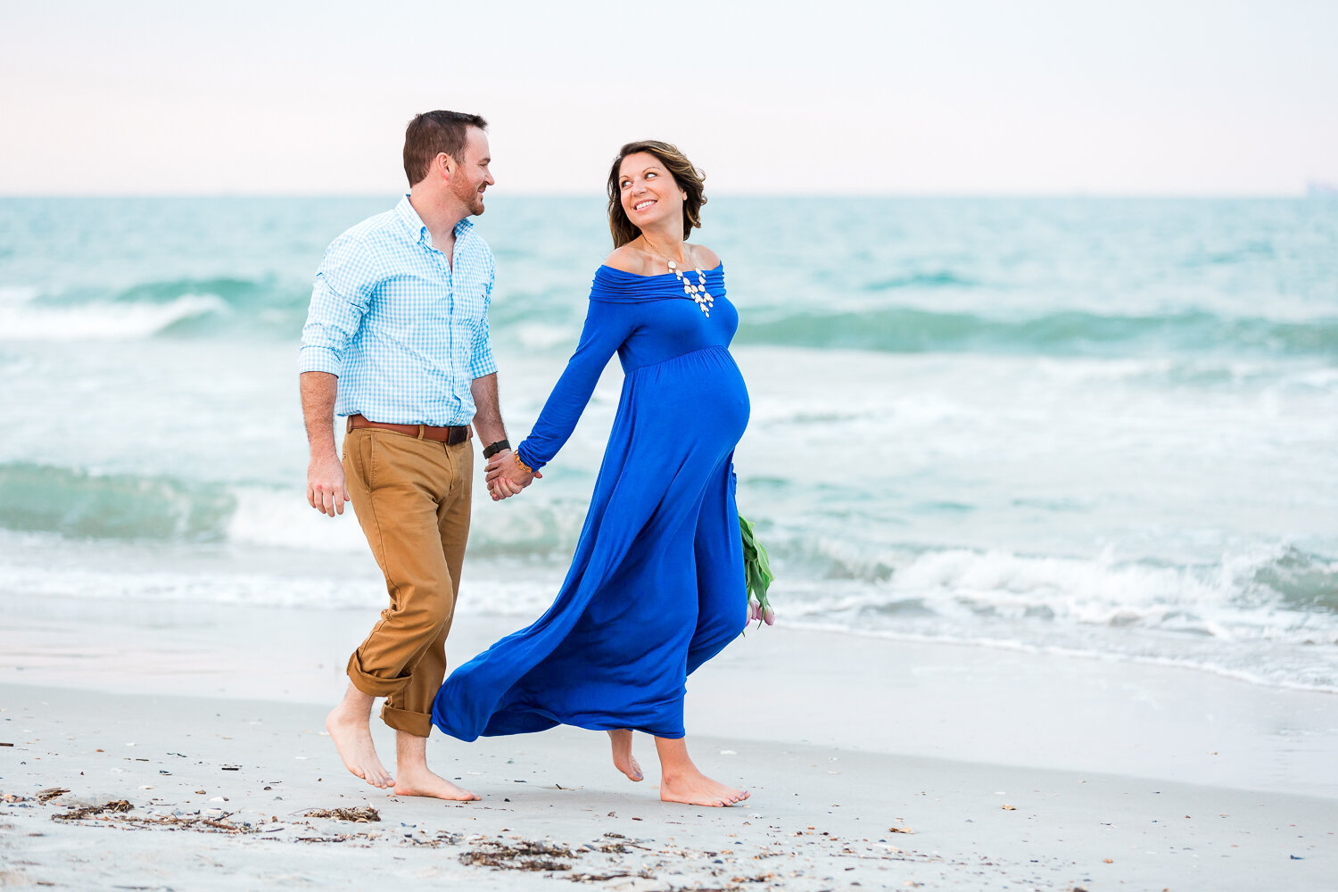 walking at the beach during the sunset maternity session in Hanna park