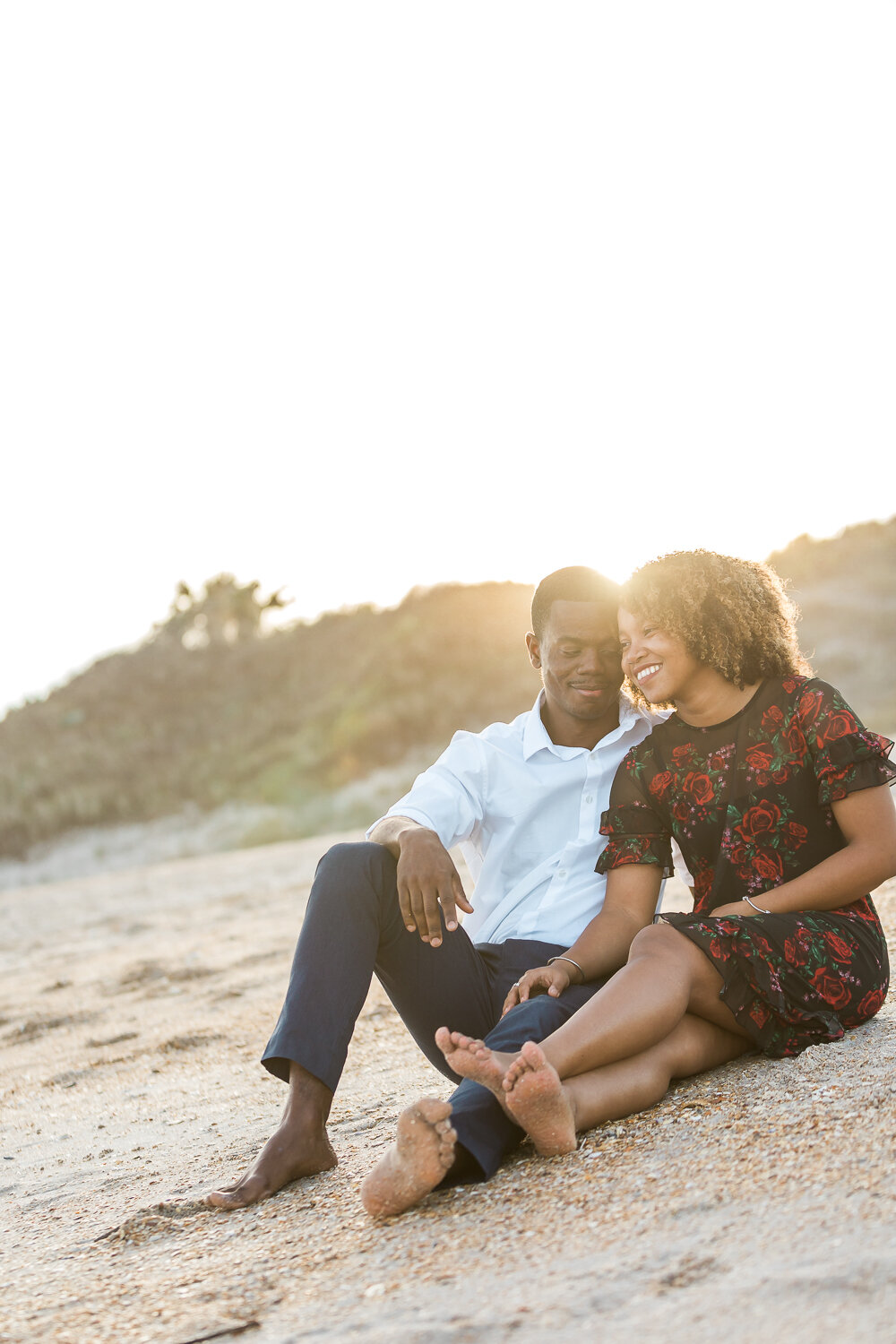 engaged couple sitting at the beach in Guana during sunset photoshoot