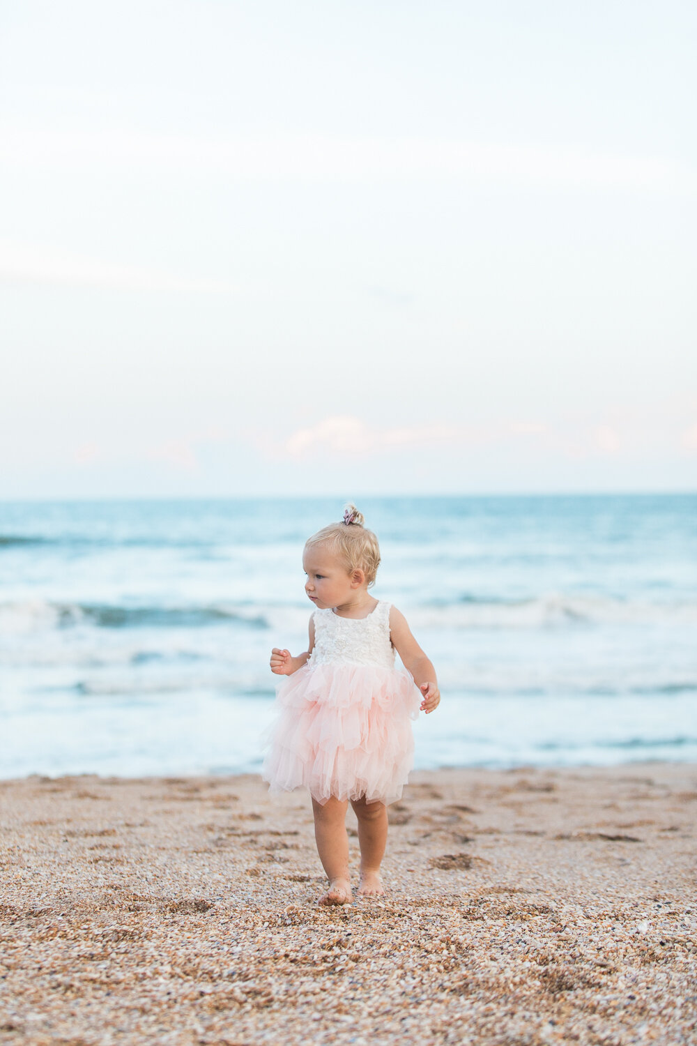 Guana beach sunset photoshoot with a toddler girl wearing a lace dress with tulle skirt - available for rent