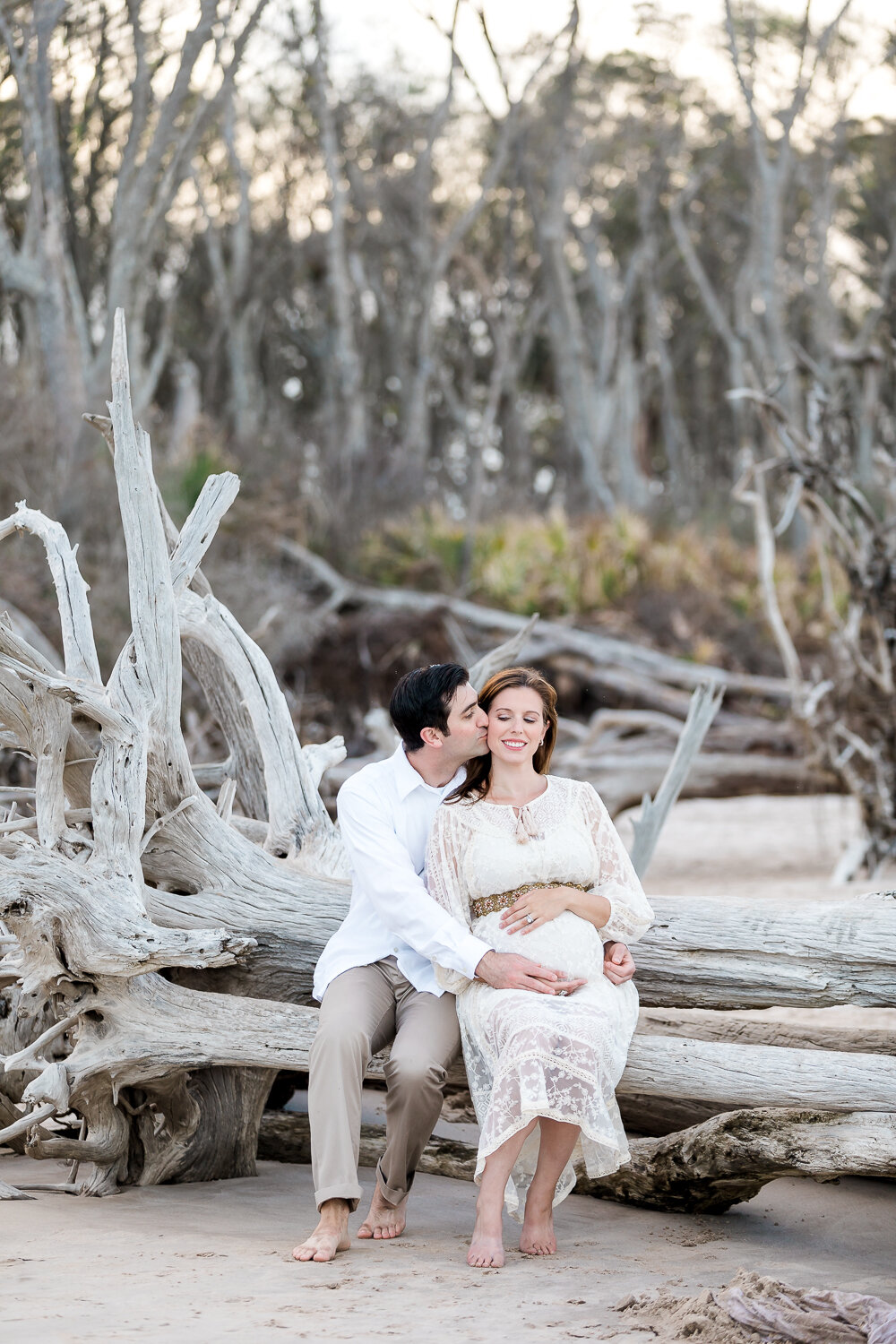 expecting parents sitting on driftwood in Big Talbot Island photoshoot