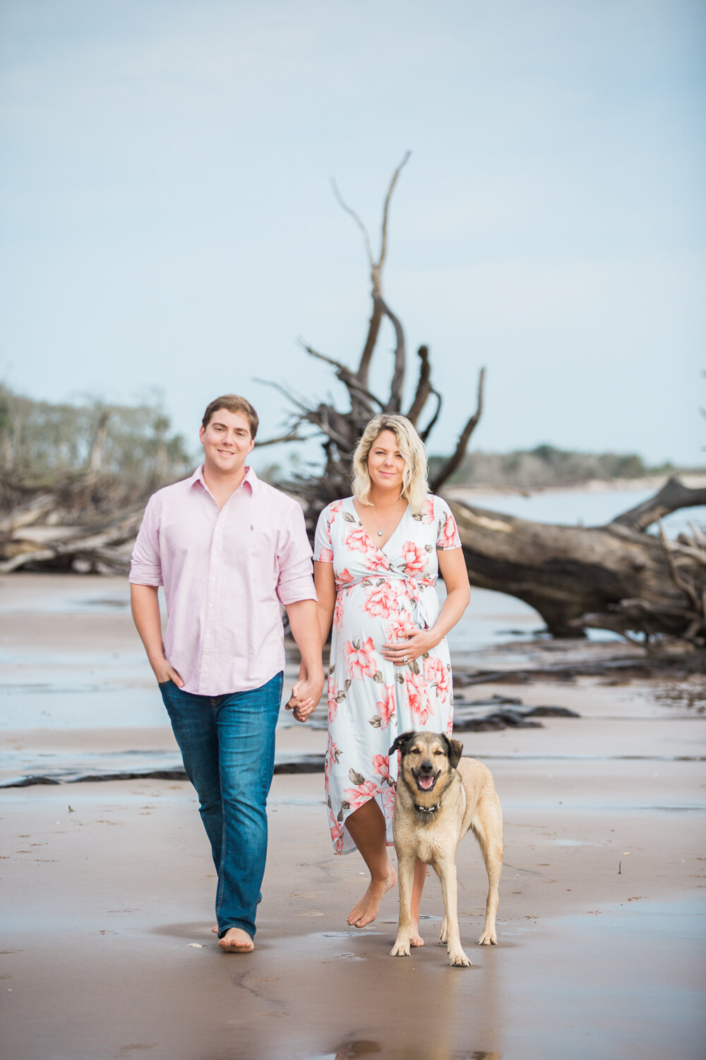 couple walking at the beach with a dog during maternity photoshoot