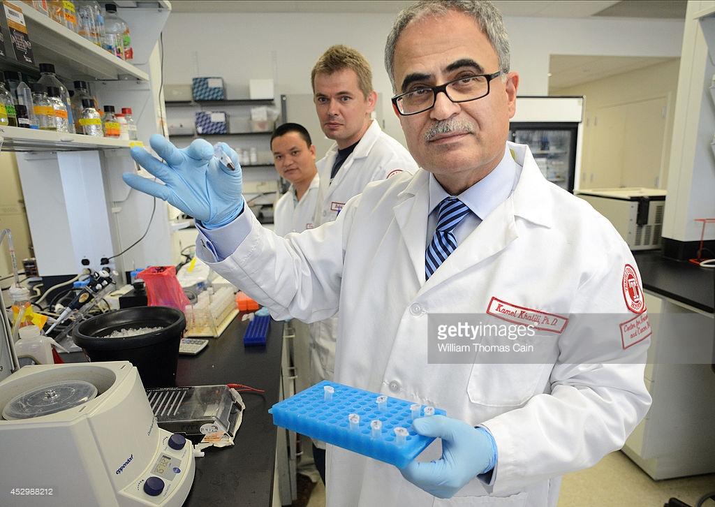 Los científicos Yonggang Zhang (Izq.), Rafal Kaminski (Centro) miran mientras el Dr. Kamel Khalili (Der.) explica el proceso de eliminación de VIH el 31 de Julio 31 del 2014 en la Universidad de Temple