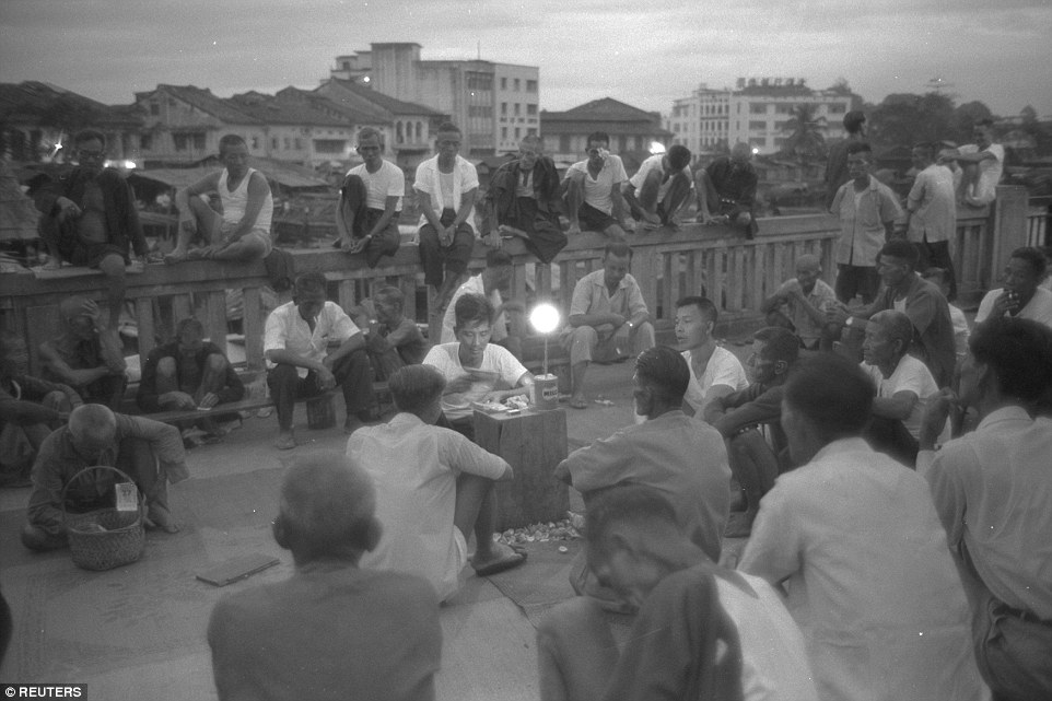 A storyteller and his audience along the Singapore River, 1960. Photo by K.F. Wong.