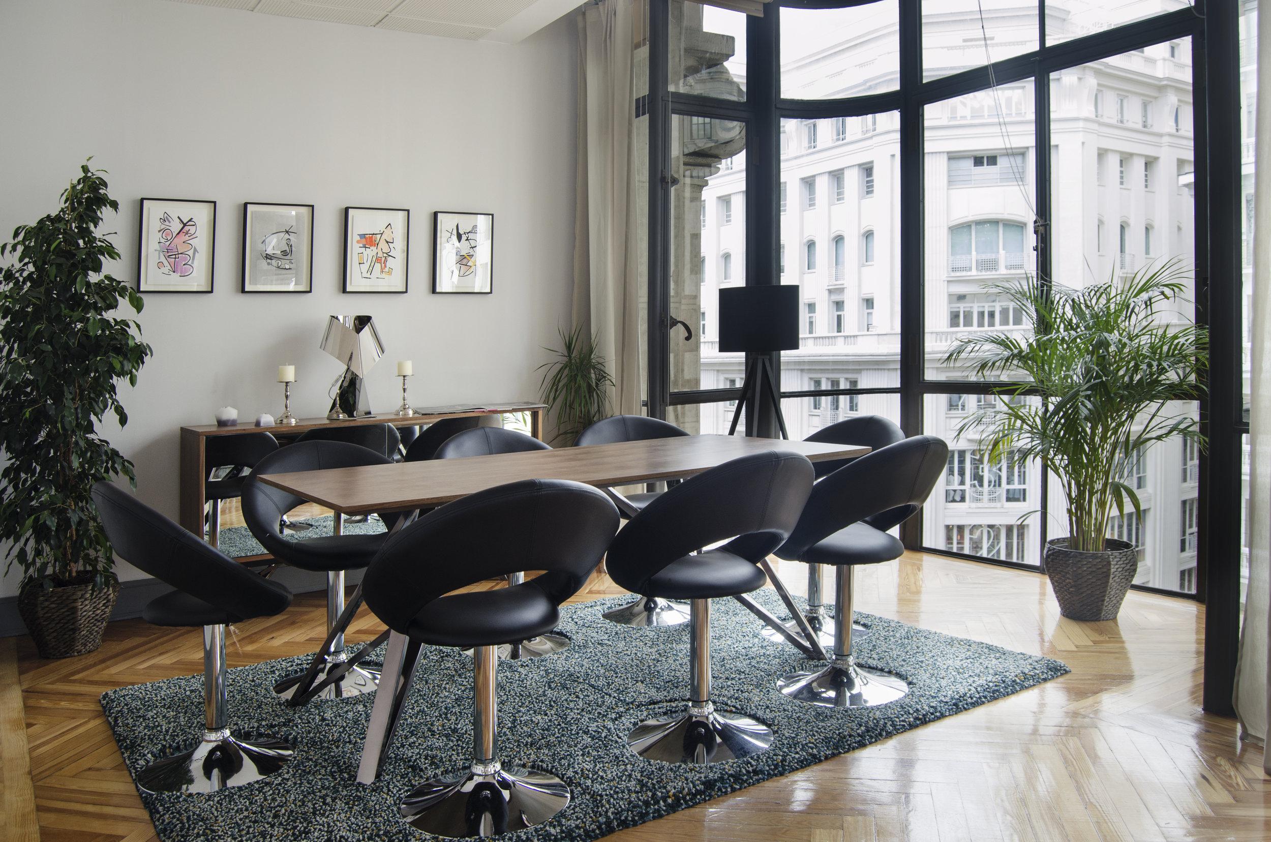 Zona de reuniones con mesa y vistas.