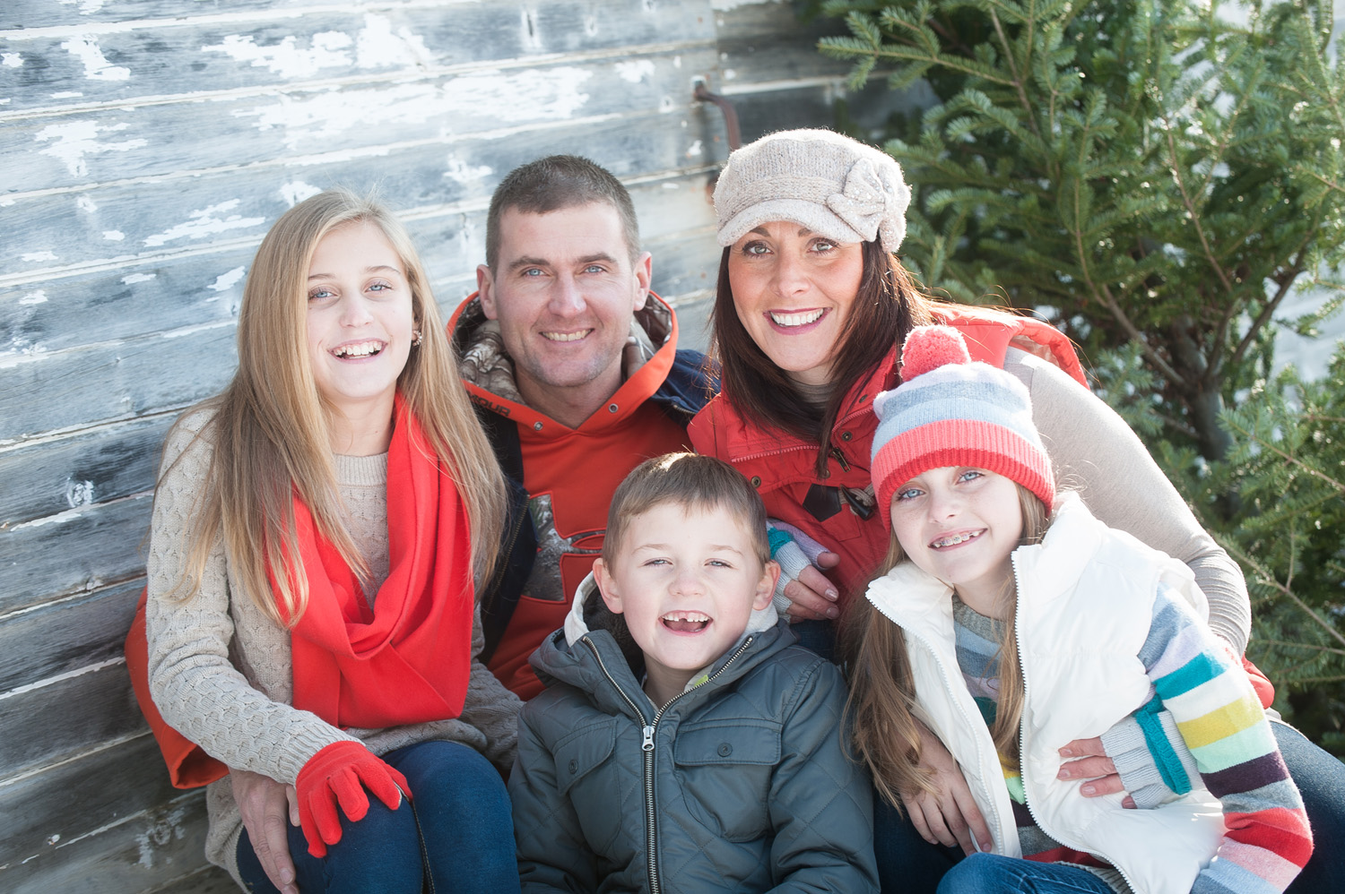 A family gathers for photos near the rustic barn during their outdoor Christmas photo session at The Gardens of Castle Rock in Northfield, MN