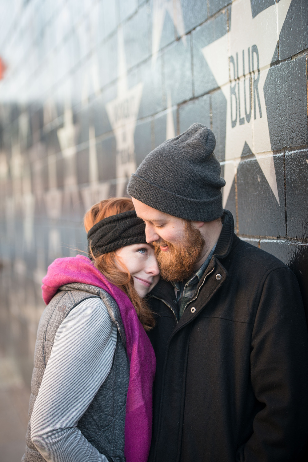 Nicole and Patrick snuggle to keep warm during their engagement photo session outside First Avenue in Minneapolis