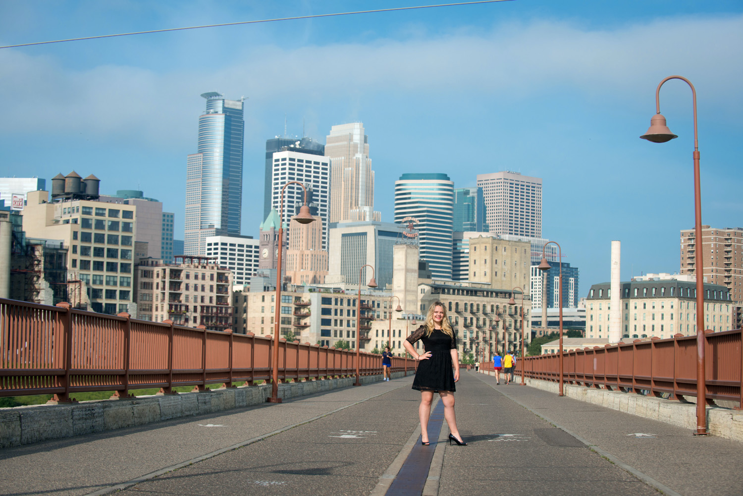 A young woman poses for a portrait in front of the Minneapolis skyline from the vantage point of the Stone Arch Bridge.