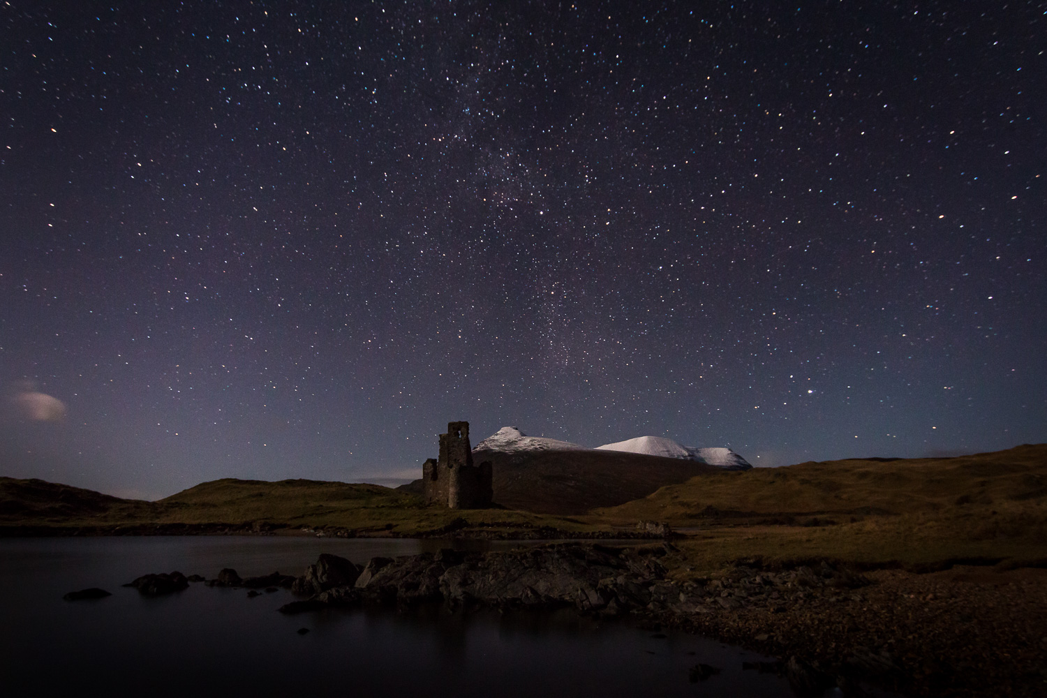 Ardvreck Castle under the Stars with a snow capped Quinag in the background.