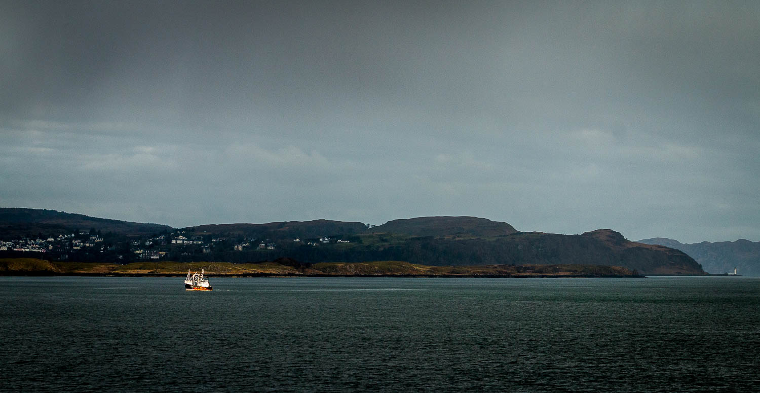 A lone fishing boat catching the early morning sun as we sail passed Tobermory.