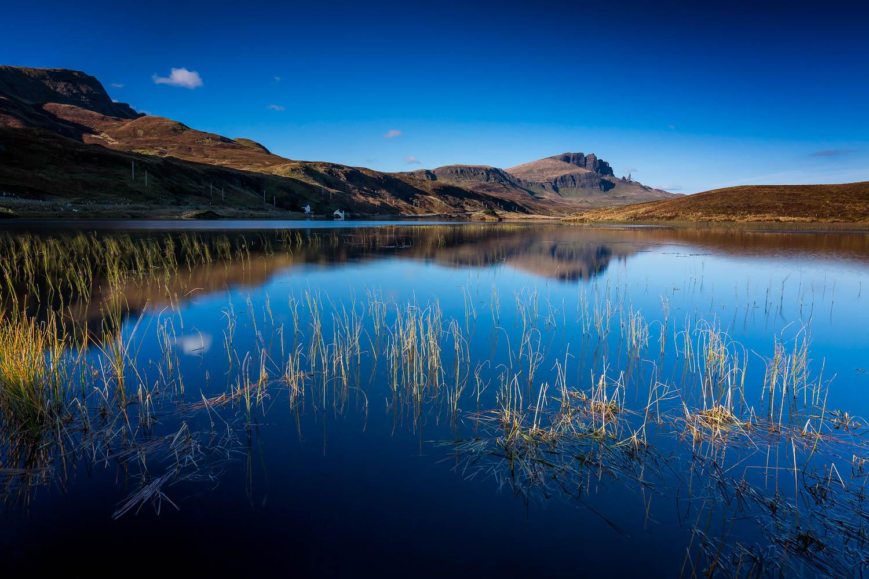 The Old Man of Storr viewed across Loch Fada under blue skies.