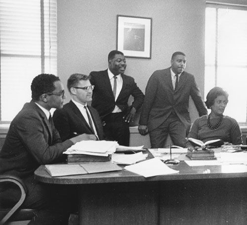Five LDF lawyers behind Thurgood Marshall's desk in 1962 (from left, clockwise) Derrick Bell, Frank Heffron, Norman Amaker, Leroy Clark, Constance Baker Motley. (Courtesy NAACP Legal Defense and Education Fund, Inc.)