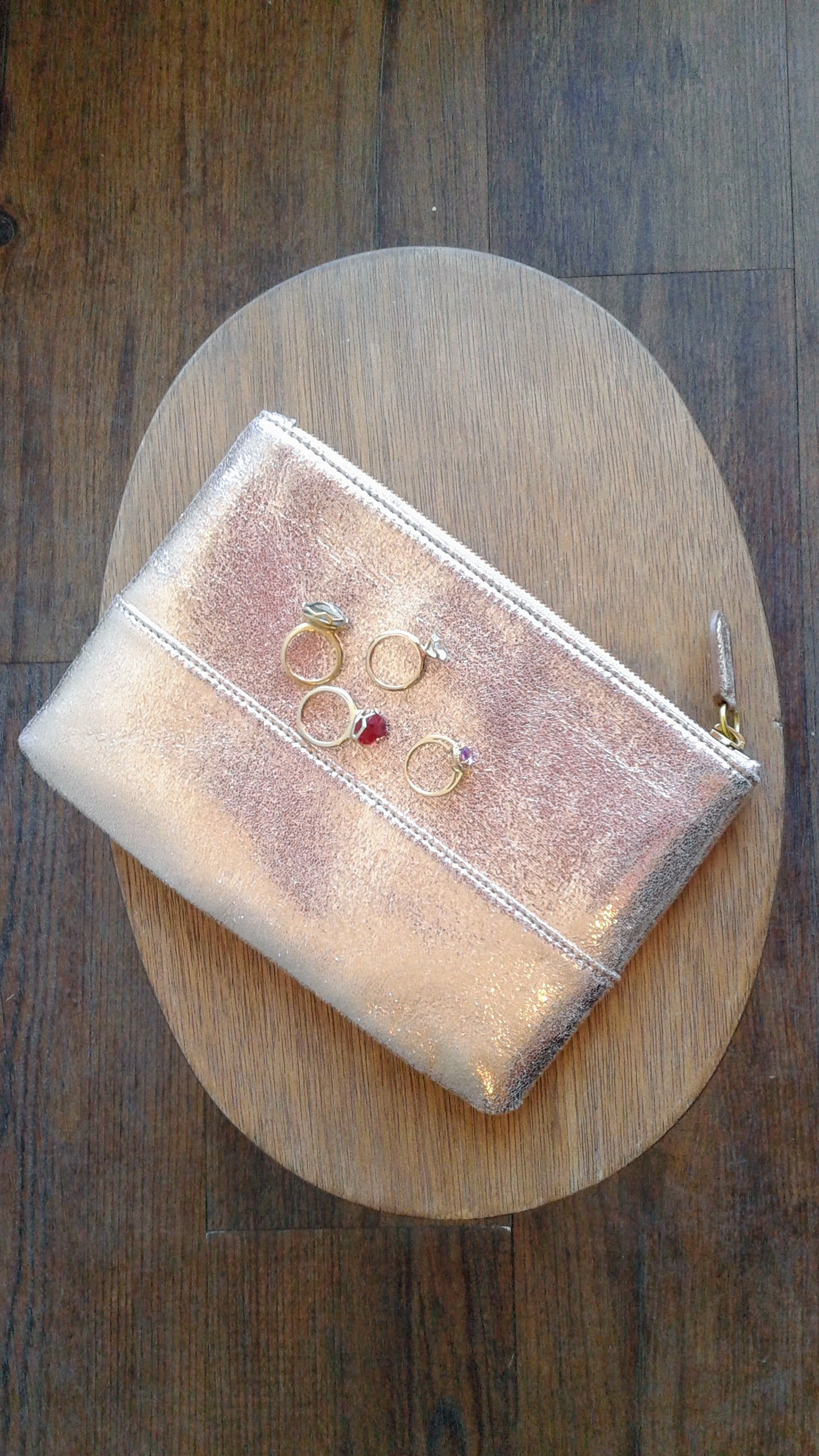 J Crew pouch, $22; Purple ring, $14; Solitaire ring, $14; Red ring, $16