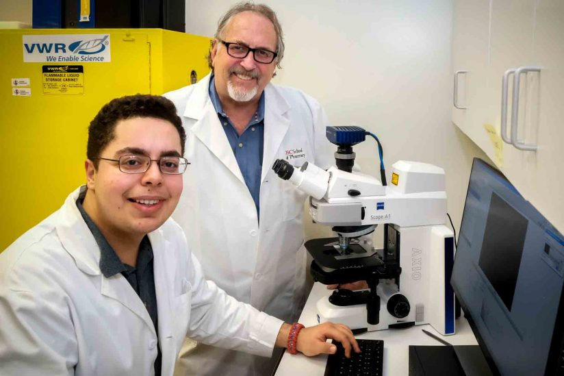 Sina Kiamehr, a senior at Francisco Bravo Medical Magnet High School, works with Daryl Davies of the USC School of Pharmacy. (USC Photo/Gus Ruelas)