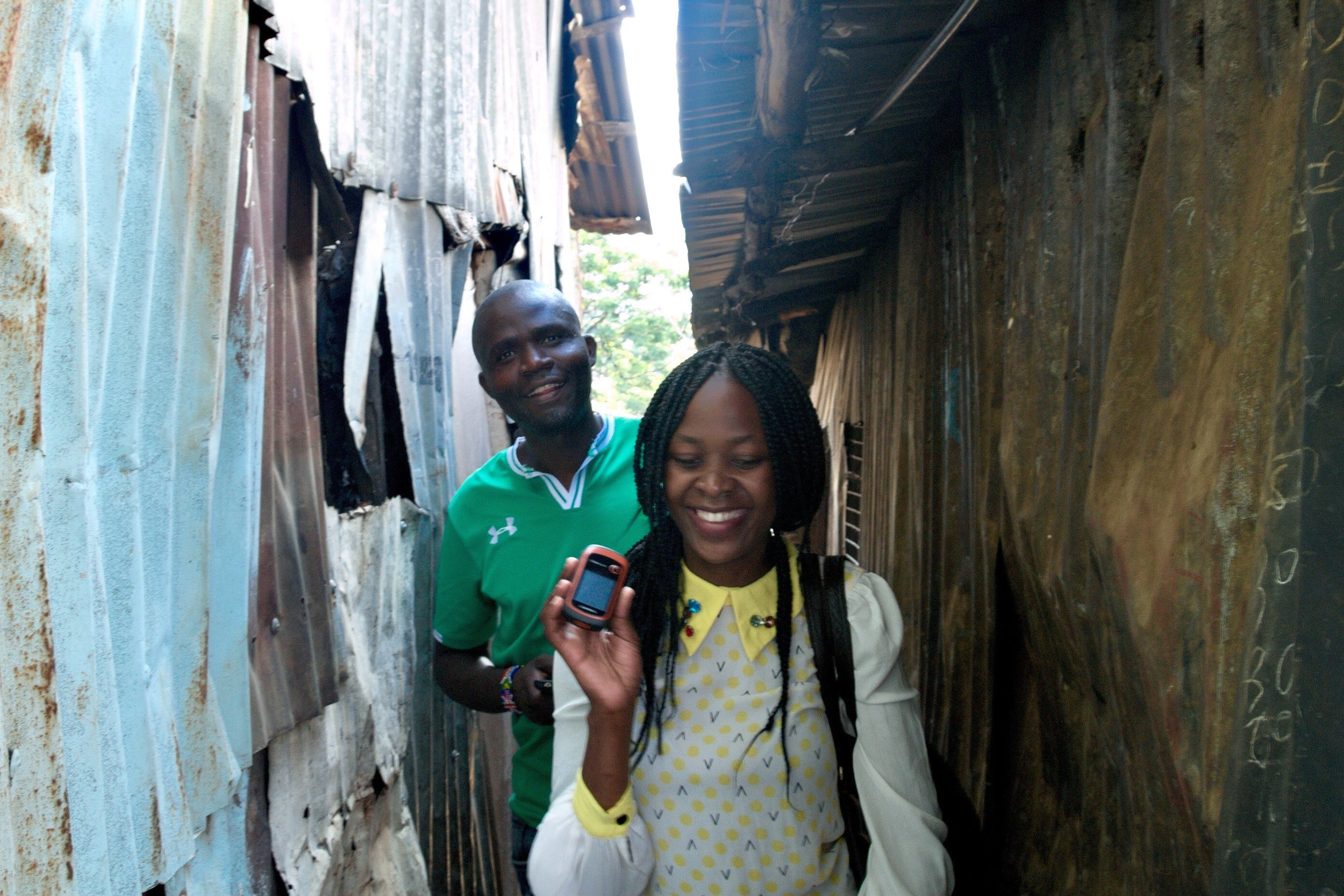 Two young people from Mathare in Nairobi, Kenya, who are mapping sanitation facilities in their community using a handheld GPS device
