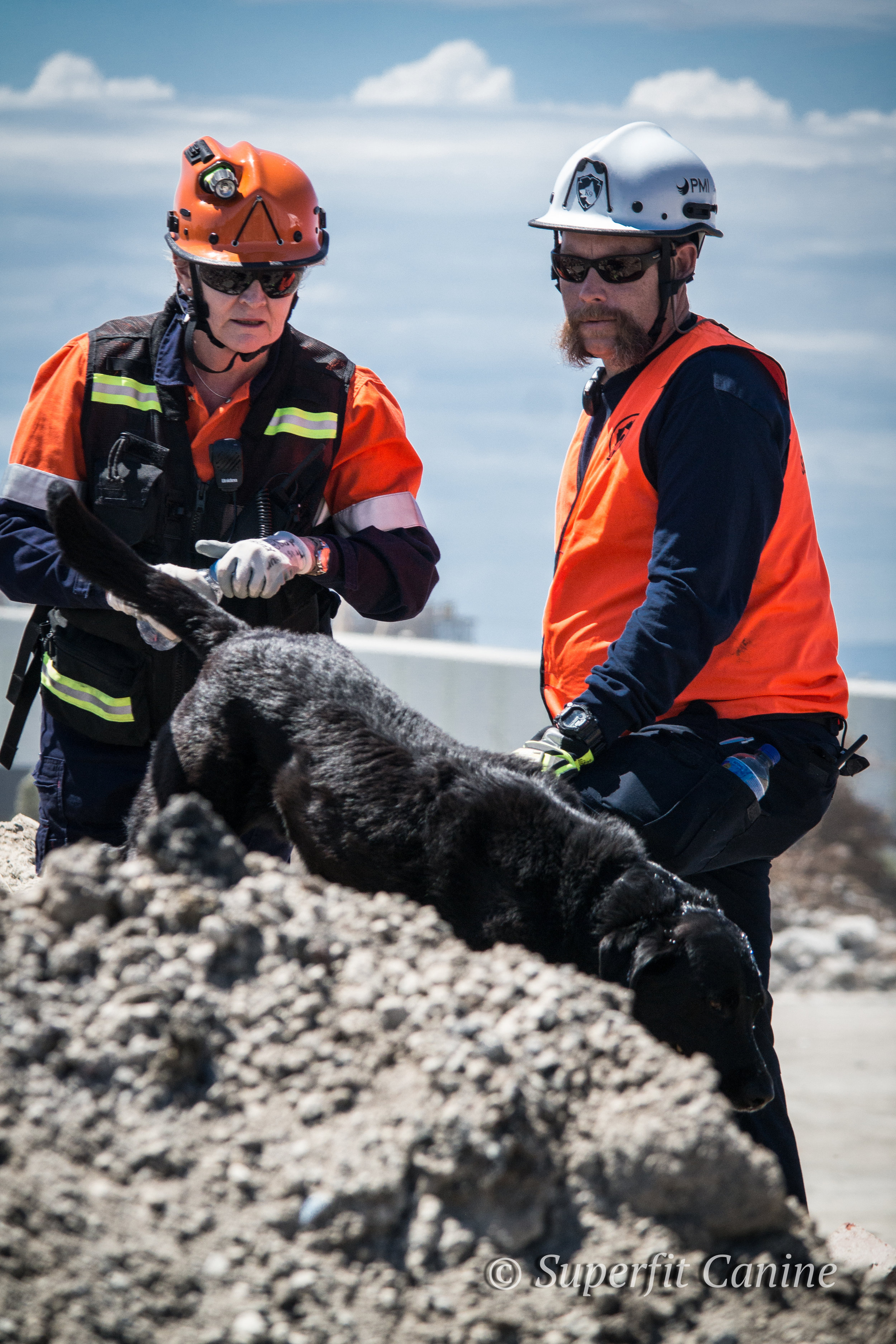 Instructor Eric Darling and handler Anne Forwood discuss search strategy as K9 BB (SARDA) navigates the rubble