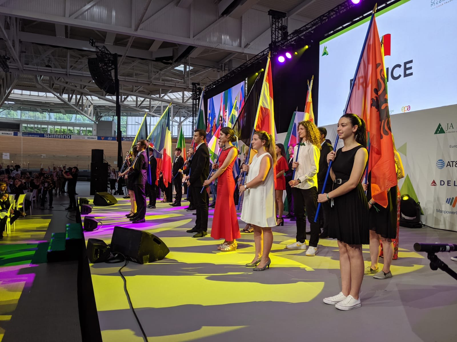 Students proudly represent their countries on stage.