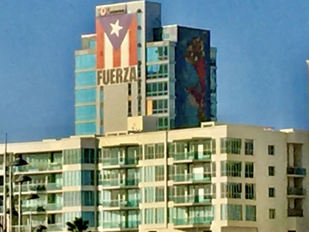 """An iconic view of a building in San Juan with the Puerto Rican flag and the Spanish word for """"strong."""" An exhortation and declaration of the enduring strength and resilience of the Puerto Rican people."""