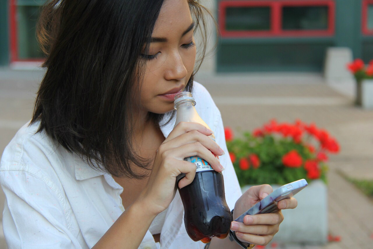 Dakota Nguyen, 18, sips on a soda while texting in front of Pitman Hall Sunday.