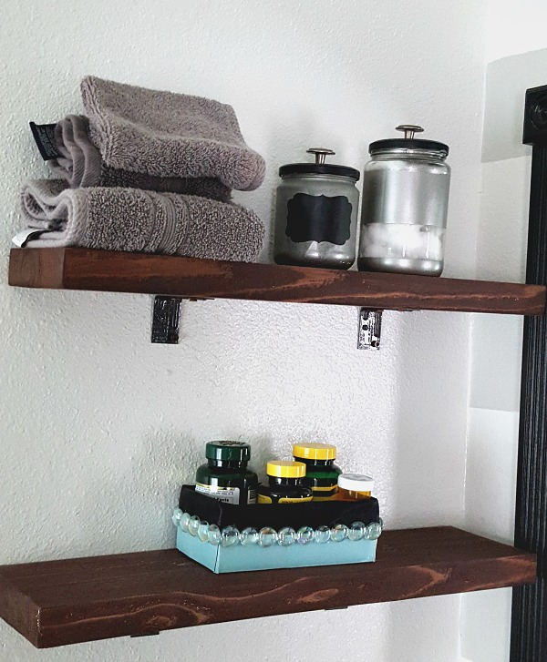 DIY bathroom shelves using 2x4s and brackets.