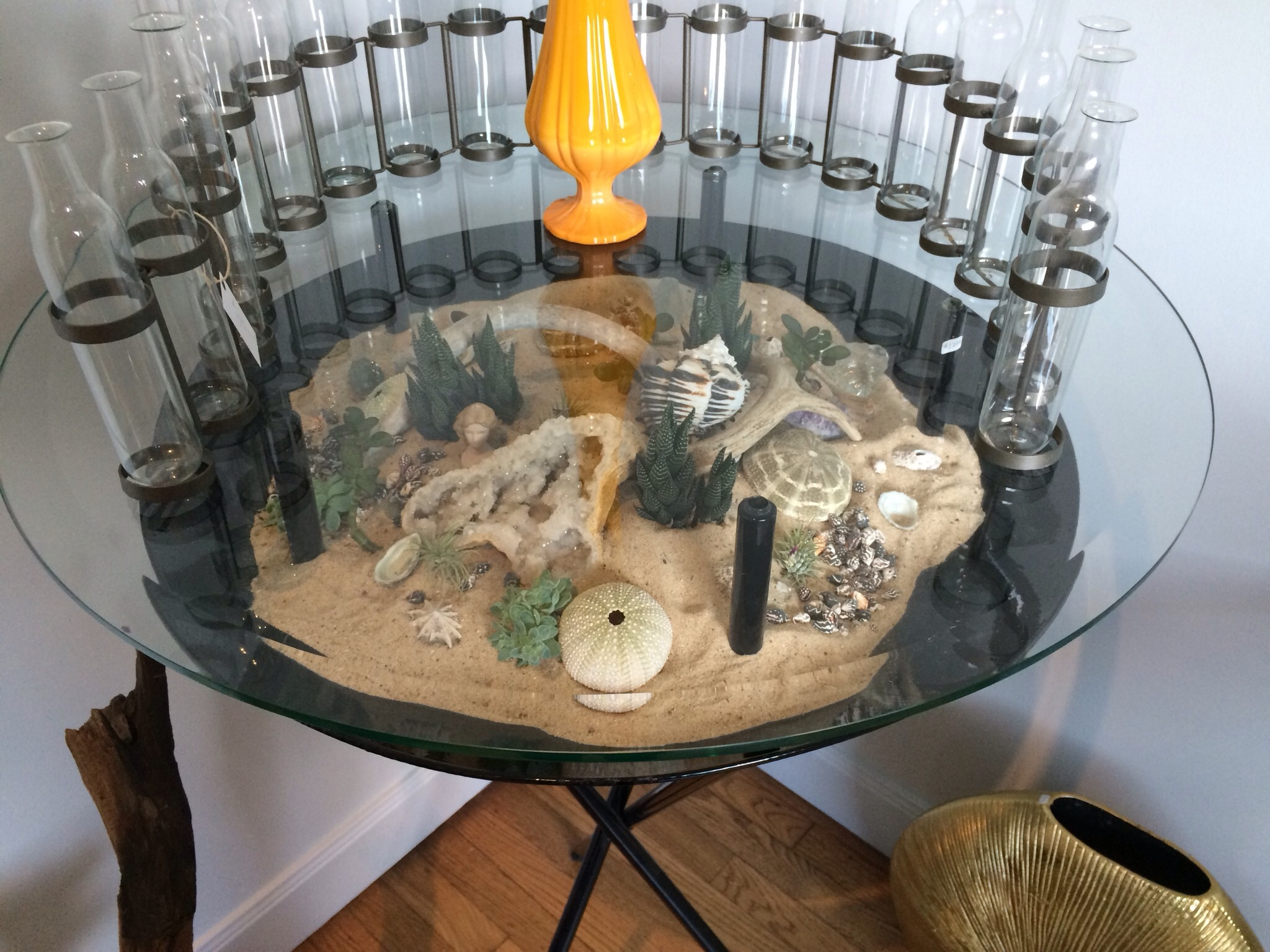 Table with a desert-scape beneath glass