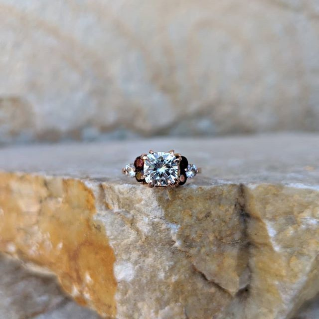 So excited to finally share some photos of this custom engagement ring I made! The center stone is a gorgeous cushion cut moissanite and it's surrounded by Idaho garnets and smaller moissanite.  So far I've been making engagement rings on a very small, custom, one on one scale. I have some ideas in the works though and I'll soon be releasing some rings of my own design!