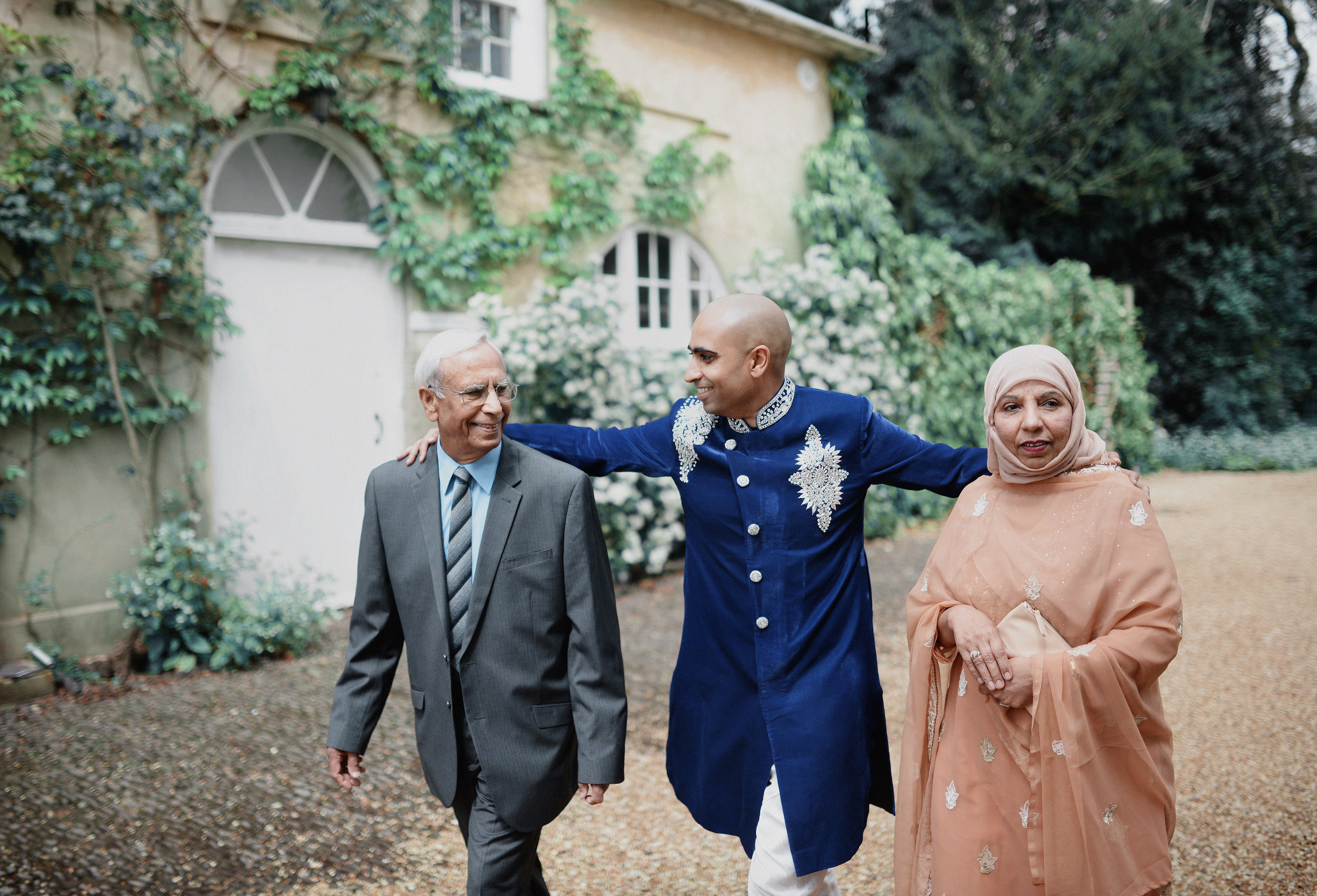 Mixed-religious Yorkshire wedding ceremony. Groom pictured wearing traditional Pakistani attire alongside his parents.