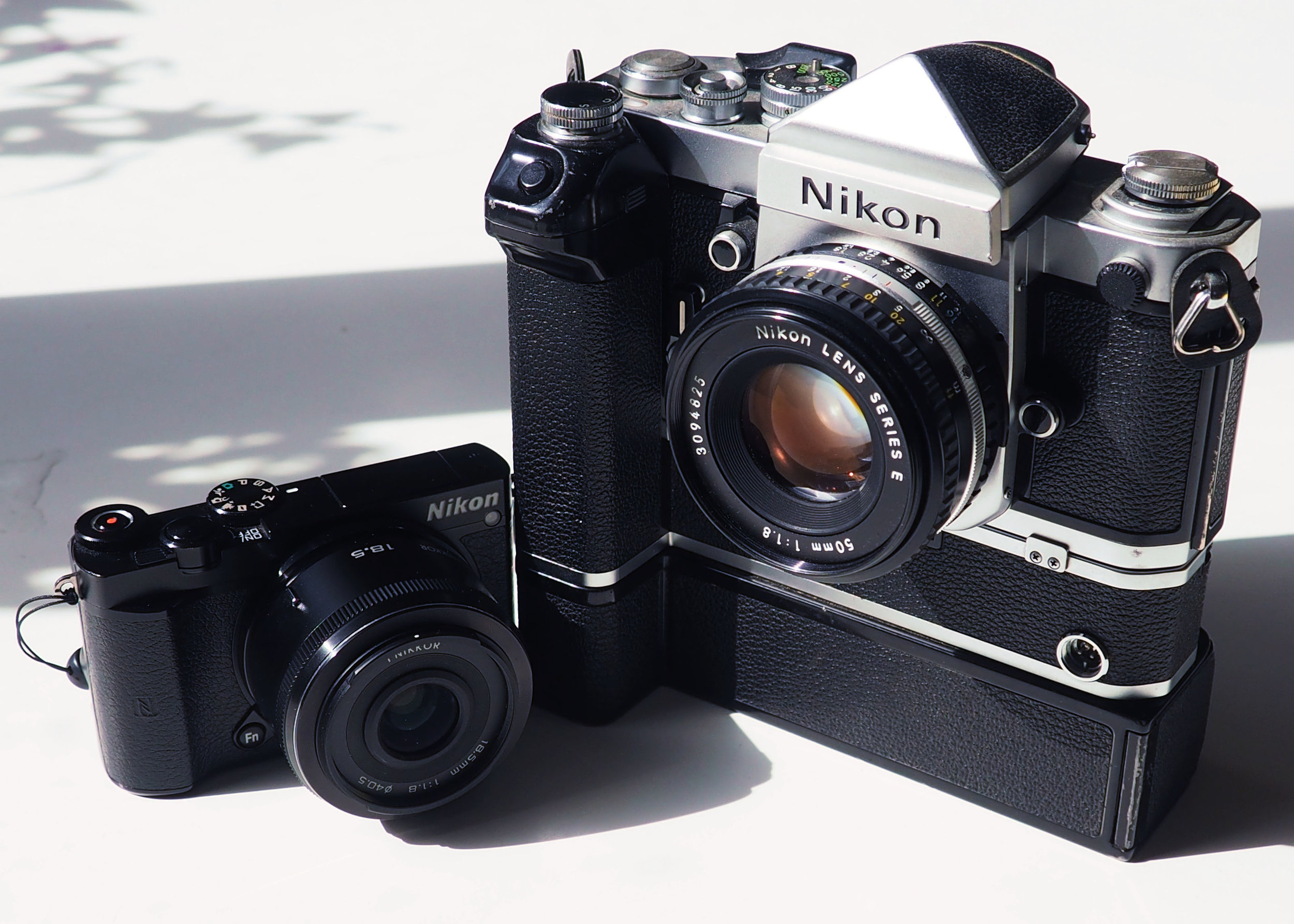 The Nikon J5 alongside the Nikon F2. The F2 will stop a bullet but only fires at 5 frames per second with the pictured MD-2 motor drive. The J5 should survive an impact from an errant ping-pong ball and can shoot at 60 frames per second. The F2 makes you feel like a conflict photographer until your shoulder starts to hurt and you realize you wouldn't last five minutes in the shit. The J5 is so light you forget you're carrying it.
