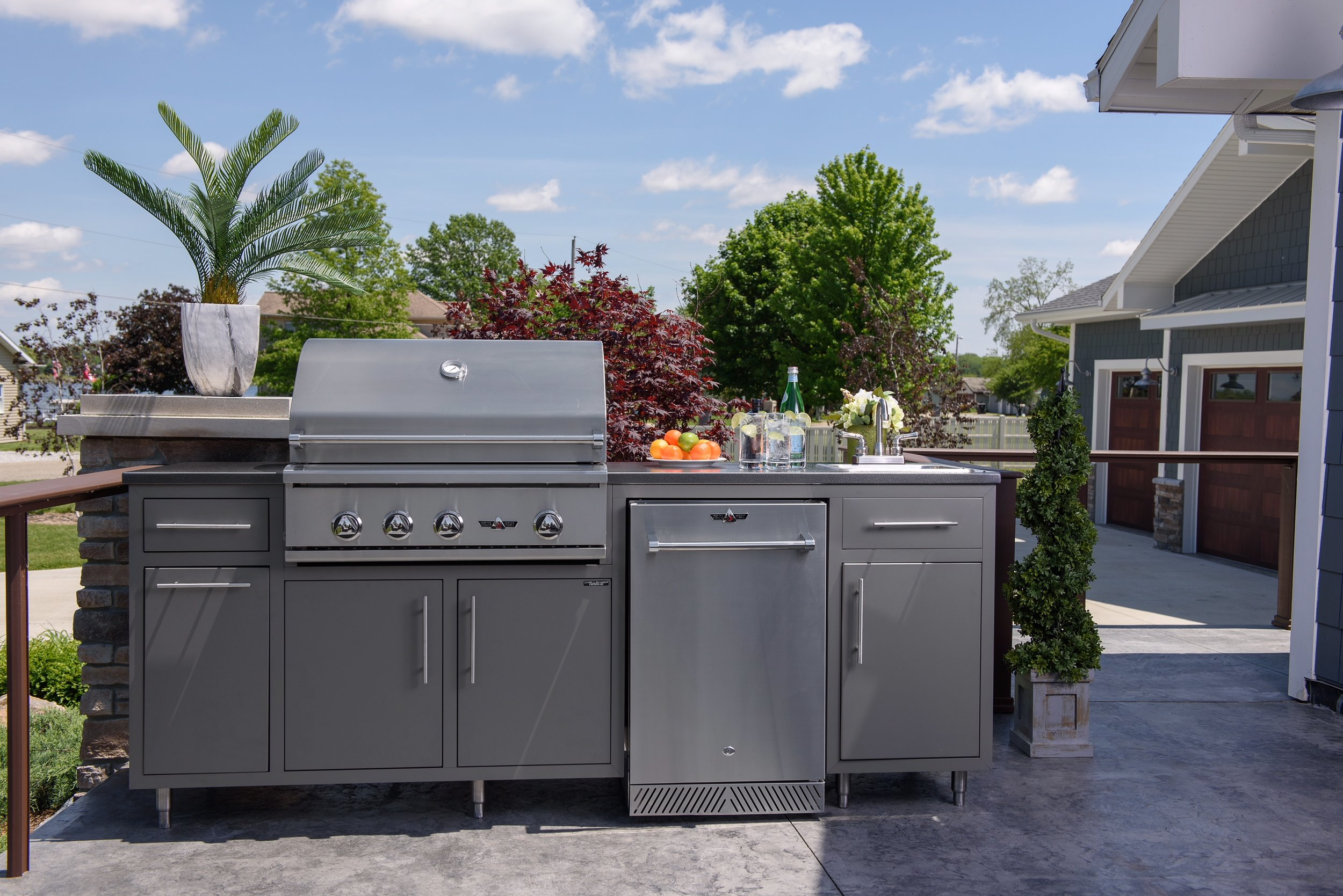 """ONLY $6,396!  Model 17COGI-89 is 89"""" wide (30"""" deep) and includes a Delta Heat 32"""" Grill (LP or NG), a 20"""" Delta Heat outdoor refrigerator, a 15"""" Sink with On-Demand Water System (5-gal fresh water tank and 5-gal grey water tank!), a 20"""" Trash drawer (can NI), two single drawers, a single door cabinet, and double door cabinet.  (With Infrared Rotisserie $6,570. With Rotisserie and Sear Zone $6,686)  Color pictured is Grey Glimmer with Silver Vein counter-top. Also available (in stock) in Cappuccino with Copper Vein counter-top!"""