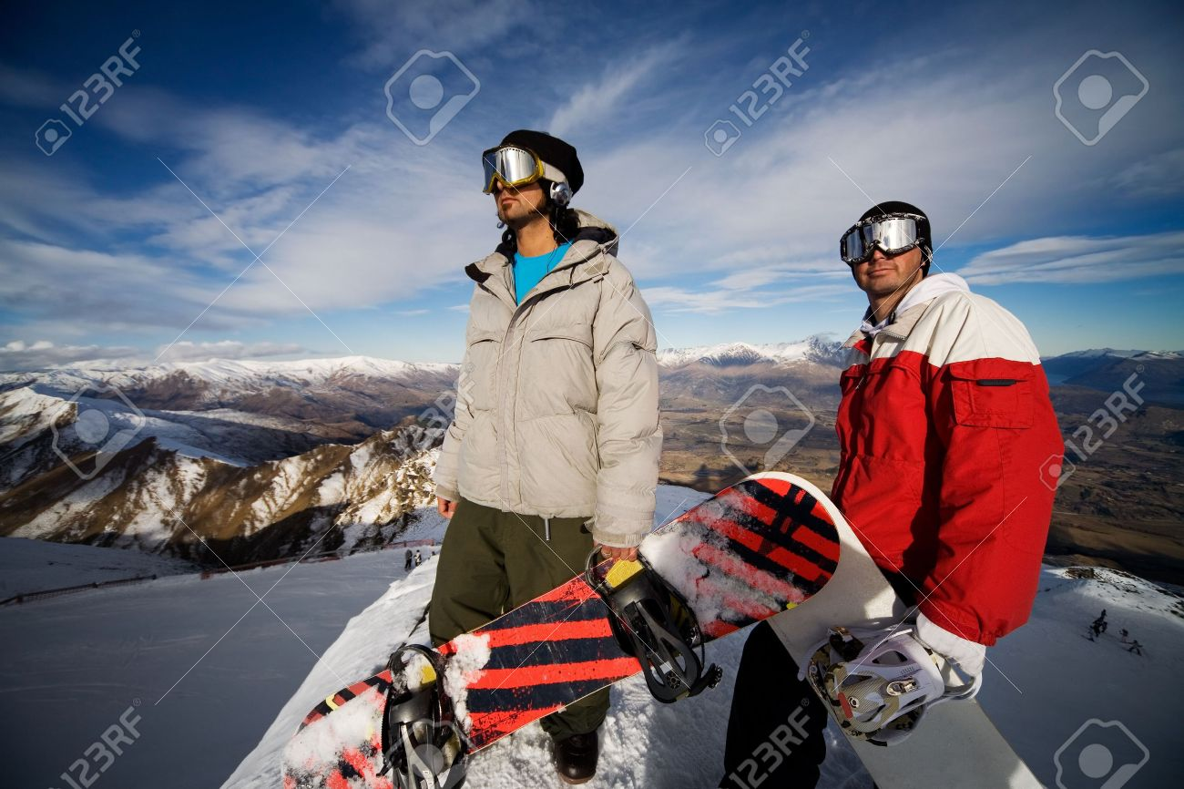 3690407-Two-snowboarders-stand-on-a-peak-over-looking-a-spectacular-view-Stock-Photo.jpg
