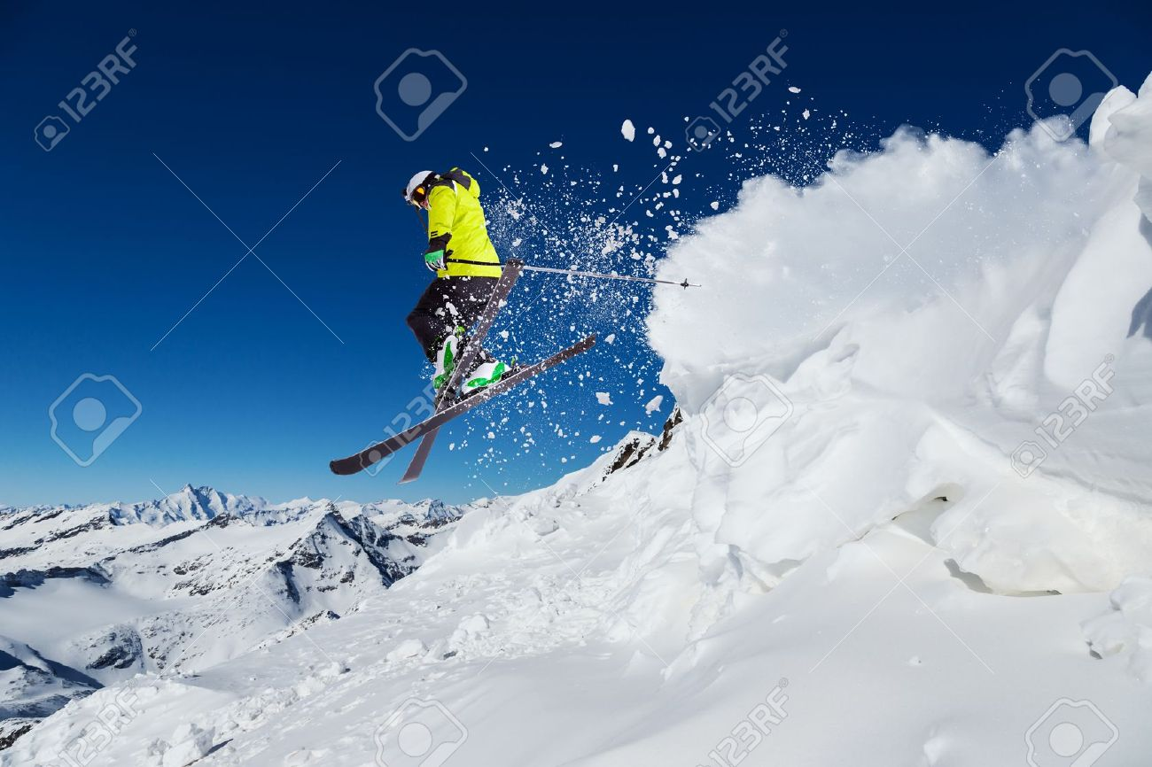 32598842-Alpine-skier-skiing-downhill-blue-sky-on-background-Stock-Photo.jpg